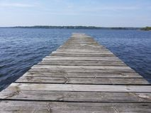 WOODEN WAY INTO THE WATER. AN EMPTY WOODEN PLATFORM FOR BOATS EXTENDING INTO THE WATER Royalty Free Stock Images