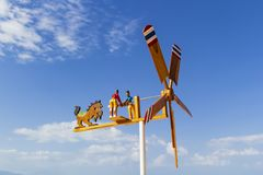 Wooden weather vane with figures of people and painted blades against. A blue sky with clouds royalty free stock photos