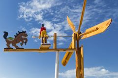 Wooden weather vane with figures of people and painted blades against. A blue sky with clouds royalty free stock image