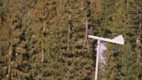 Wooden weather vane spinning in the wind in winter. Old homemade windmill made of wood, twisted in the wind and reeling against the backdrop of trees and houses stock video footage