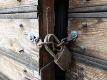 Wooden weathered antique gates closed with padlock.  royalty free stock photos