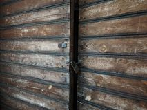 Wooden weathered antique gates closed with padlock.  stock image