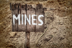 Wooden weathered warning sign for mines. In front of a minefield Stock Images