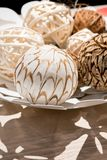 Wooden weave decorative balls in white decorative dish. On wood table Royalty Free Stock Images