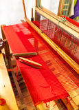 Wooden weaving shuttle on an old manual loom. Vintage wooden loom weaving prepared for the red carpet. Wooden weaving shuttle on an old manual weaving machine royalty free stock photos
