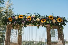 Wooden wedding arch in Provence style decorated with flowers, sunflowers and other summer flowers stock photography