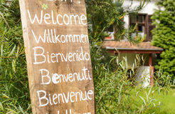 Wooden welcoming sign. Welcoming sign written with white paint on an old piece of wood in different languages stock photography