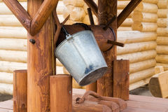 Wooden well with a bucket. Wooden well with a steel bucket Royalty Free Stock Photo