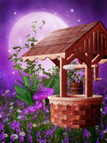 Wooden well on a meadow. Wooden well on a purple meadow with mushrooms and flowers Royalty Free Stock Photos