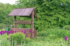 Wooden well in the village. Wooden well on the background of green foliage stock image
