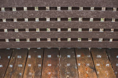 Wooden wet bench in the summer park. Closeup with reflections.  Stock Image