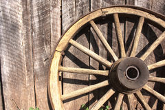 Wooden wheel against barn. Old wooden wheel leaning against weathered barn Stock Photo