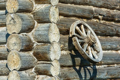 Wooden wheel on the log wall. Stock Photo