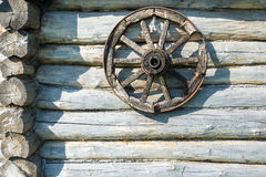 Wooden wheel on the log wall. Royalty Free Stock Photos