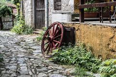 Wooden wheel in the old greek traditional village. Pretty village greek style - artwork in retro style Royalty Free Stock Photo