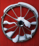 Wooden wheel on the red wall Stock Photos