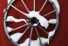 Wooden wheel on red wall with snow Royalty Free Stock Photo