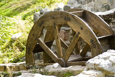 Wooden wheel and stone walls Stock Image