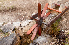 Wooden wheel turning in a small stream Royalty Free Stock Photography