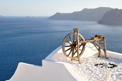 Wooden wheel with a view. A great view from the island of Santorini, Greece Royalty Free Stock Photography