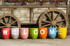 Wooden wheels and WELCOME sign. WELCOME sign in front of Wooden wheels Stock Images
