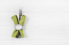 Wooden white background for a menu card with cutlery in apple gr. Wooden white background for a menu card fork, knife and a apple green napkin with ring Royalty Free Stock Images
