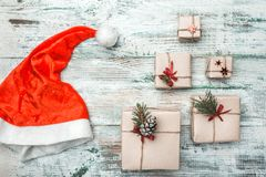 Wooden white background. With modern texture. Space for Santa`s message. Christmas greeting card, Handmade items. Many gifts. His Santa`s hat. Xmas and Happy stock images
