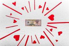 Wooden white background with red hearts and fifty dollars . The. Concept of Valentine Day Royalty Free Stock Images