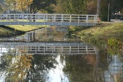 Wooden white bridge over ditch in the autumn season in public park Schakenbosch in Leidschendam. Wooden white bridge over ditch in the autumn season in public stock image