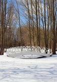 Wooden white bridge over snowy frozen water Royalty Free Stock Photos