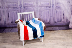 Wooden white chair covered with colored plaid tepym. Royalty Free Stock Images