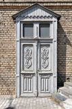 Wooden white door with floral patterns. Old vintage wooden white door with floral patterns on the brick wall background. Grodno, Belarus Royalty Free Stock Images