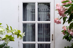 Wooden white door with pink flower Stock Photos