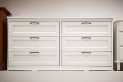 Wooden white dresser. Modern chest of drawers royalty free stock image