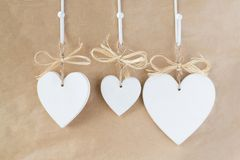 Wooden white hearts. With bows hang Royalty Free Stock Photos