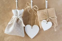 Wooden white hearts and gifts. With bows hang Royalty Free Stock Images
