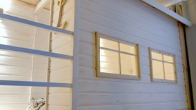 Wooden white house in kids room with windows and bed inside. Wooden white house in kids room with windows and bed inside stock video footage