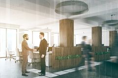 Wooden and white open space office corner toned. White and wooden open space office with a concrete floor with white lines marking space, a row of computer desks Royalty Free Stock Image