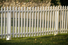 Wooden White Picket Fence At Sunset. A wooden white picket fence in a well kept yard during the golden hour time, just before sunset, on an early Autumn day Stock Image