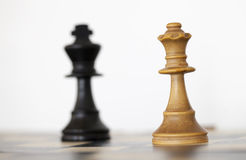 Wooden white queen and black king chess pieces. On chess board Royalty Free Stock Images