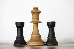 Wooden white queen and black rooks chess pieces. On chess board Royalty Free Stock Photo