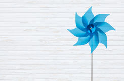 Wooden white shabby background with a blue windmill or pinwheel. Blue windmill like a flower isolated on a white wooden shabby background Stock Photos