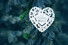 Wooden white snowflake on a Christmas tree in the form of a heart with text. Greetings card on the Christmas tree Royalty Free Stock Photography