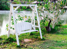 Wooden white swing. On the grass of rural village Stock Photography