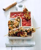 Chicken skewers in spicy marinade and tomato dip. stock photo