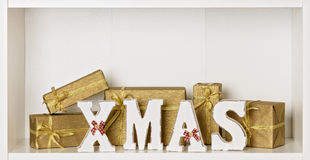 Wooden white XMAS letters on a white background with Packed gift Stock Image