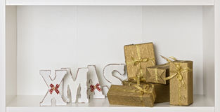 Wooden white XMAS letters on a white background with Packed gift Royalty Free Stock Image