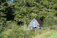 Wooden wigwam. A Wooden wigwam, nestled in trees of Scotland Stock Photos
