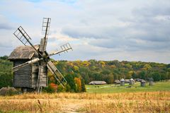 Wooden windmill. An old wooden windmill near the autumn village stock images