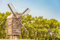 Wooden windmill on a background of green trees Royalty Free Stock Photo